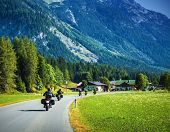 Group of motorcyclists on the road pass across mountainous village, Europe, Alps, active lifestyle,