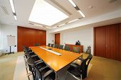Long wooden table, modern armchairs in empty room for business meetings.