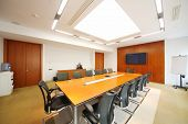 Long wooden table, black armchairs in light room for business meetings.