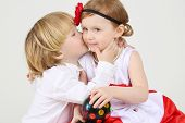 Little boy kisses pretty girl with ball-shaped lamp on white background.