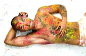 Attractive Young Man Shirtless Laying On The Floor, Skin Painted All Over With Colors