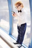 Little cute girl in glasses holds black cell phone and stands near window.