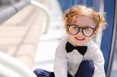 Little cute red hair girl in glasses sits on floor in gallery near window.