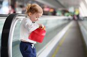 Little red hair girl takes out credit card from red purse on travelator.