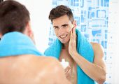 Portrait of a young man in the bathroom applying after shave