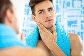 stock photo of grooming  - Young handsome man touching his smooth face after shaving - JPG