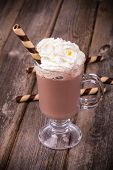 Hot chocolate with whipped cream topping, in glass with  rolled wafer. Vintage effect processing