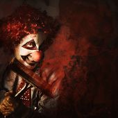 picture of freaky  - Evil monster clown washing splattered glass with squeegee and sinister smile - JPG