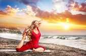foto of raja  - Yoga raja kapotasana pigeon pose by young woman with long hair in red cloth on the beach near the ocean at dramatic sunset background - JPG
