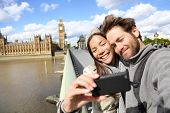 London tourist couple taking photo near Big Ben. Sightseeing woman and man having fun using smartpho