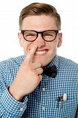 stock photo of nostril  - Young guy fingering in his nostril over white - JPG