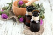 image of scottish thistle  - Medicine bottles and mortar with thistle flowers on wooden background - JPG