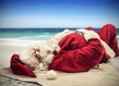 foto of ironic  - Santa Claus relaxes lying on the beach - JPG