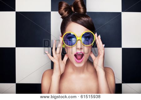 Attractive surprised young woman wearing sunglasses on checkered background, beauty and fashion conc poster