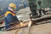 adult industrial worker at spot welding machine in factory workshop