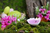 Conceptual Easter composition. Burning candle in egg, Easter eggs and flowers on green grass background, close-up