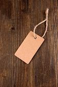 Brown tag on color wooden background