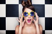stock photo of brunette hair  - Attractive surprised young woman wearing sunglasses on checkered background - JPG