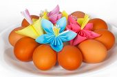 Easter eggs on the plate with a paper flower