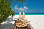 Woman at beautiful beach lying on chaise lounge