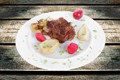 meat beef bourguignon in wine with artichoke and marinated vegetables on white plate isolated over white background