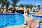 Sunbathing by the hotel tourist resort swimming pool, mans legs lying down on a sunlounger looking o