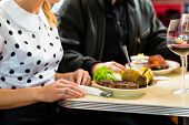 stock photo of diners  - Young couple eating fast food and drinking red wine in a American retro fast food diner - JPG
