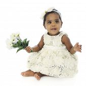 A beautiful baby girl dressed up and barefoot happily holding a small bouquet of flowers.  On a whit