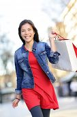 Shopper - woman shopping outside holding shopping bags walking outdoors smiling wearing denim jacket. Beautiful mixed race Asian Caucasian girl in her 20s.
