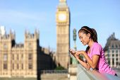 London lifestyle woman runner listening to music on smart phone near Big Ben. Female running girl re