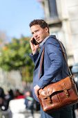 Business man on smartphone walking in street talking on mobile smart phone smiling wearing jacket an