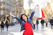 Happy shopping woman on La Rambla street Barcelona. Shopper girl holding shopping bags up excited ou