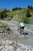 Mountain Biker Riding Through Stream