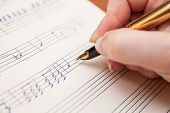 picture of compose  - Hand pointing with pen to music book with handwritten notes - JPG
