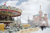 MOSCOW, RUSSIA - DEC 8, 2013: Carousel and St. Basil cathedral during Christmas fair (area of fair i