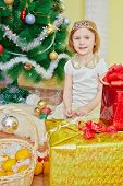 pic of tangerine-tree  - Smiling little girl with crown on her head sits on furry rug among gift boxes and wicker baskets with tangerins under christmas tree - JPG