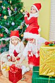 Two little girls in santa caps with strings in form of plaits examine gift boxes, boy decorates chri
