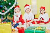 Two little girls and one boy in santa caps sit on furry rug under decorated christmas tree poster