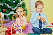 picture of tangerine-tree  - Little girl and boy sit on furry rug under christmas tree - JPG