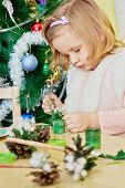 Little girl paints revealed pine-cone with green gouache sitting at wooden table with children jobbi