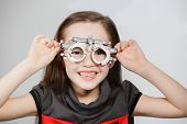 stock photo of ophthalmology  - Young girl smiling while undergoing eye test with phoropter - JPG