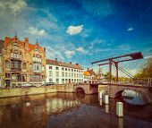 Vintage retro hipster style travel image of canal with old bridge. Bruges (Brugge), Belgium with gru