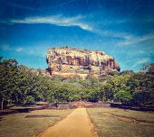 Vintage retro hipster style travel image of famous ancient Sigiriya rock with grunge texture overlaid. Sri Lanka
