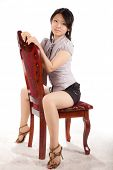 Beautiful girl in the studio sits on a chair