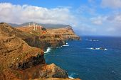 Eastern tip of the island of Madeira. Rocks steeply in the blue waters of the Atlantic Ocean.  Over a cliff on the ocean breeze are the windmills