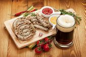 Grilled sausages with ketchup, mustard and mug of beer. Over wooden table background