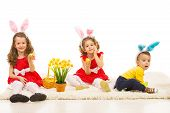 stock photo of bunny ears  - Three kids with bunny ears and Easter basket sitting on the carpet home - JPG