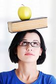 Student with an apple and book on her head