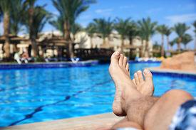 image of pov  - Sunbathing by the hotel tourist resort swimming pool - JPG