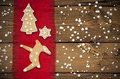 picture of ginger bread  - Ginger Bread Cookies on Red Drapery on Wood in the Snow Winter Background - JPG